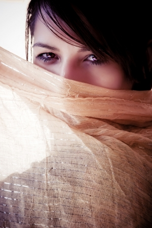 middle eastern clothing: Young woman behind arab veil. Stock Photo