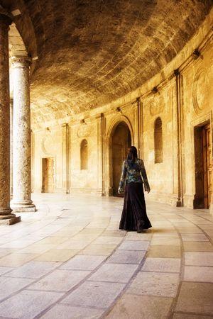 Young woman walking among old walls. photo