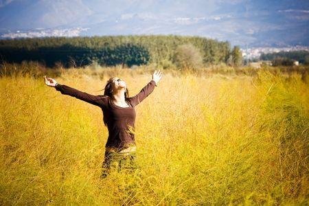Mujer sensación de libertad rodeado por el otoño de colores.