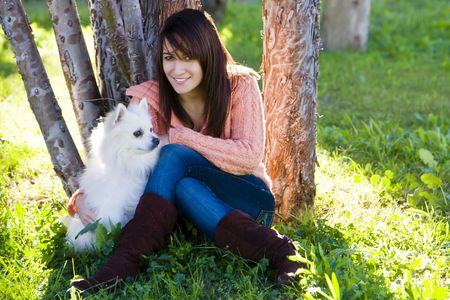 Young beautiful woman with her pet in the park. photo
