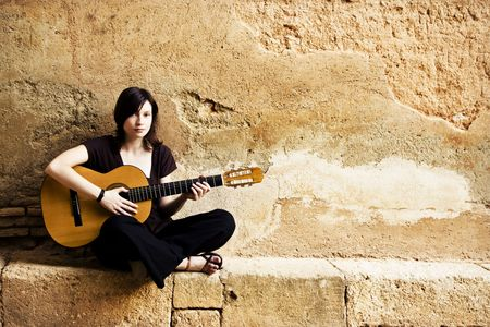 vagabond: Young female guitar performer posing with her instrument. Stock Photo