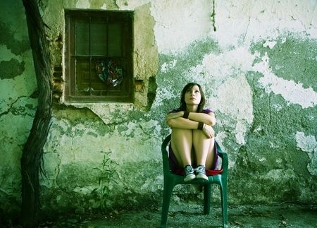 Young sad woman sitting in old dirty place photo