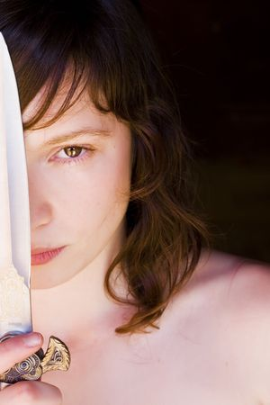 expressing: Young blond woman with a knife over her face Stock Photo