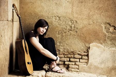 m�sico: Lone triste guitarrista situado en el antiguo brickwall. Foto de archivo