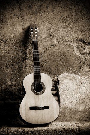 Classic guitar on wall, sepia toned. Stock Photo