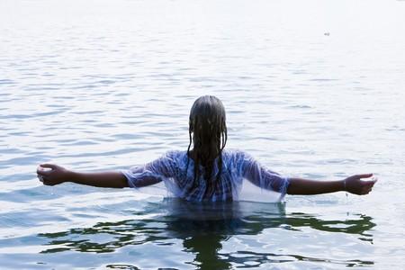 battesimo: Giovane donna con braccia sollevate in acqua.