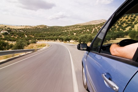 faster: Cruising the countryside in a blue car at high speed.