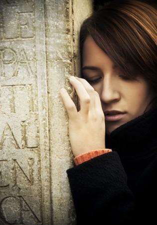 occhi tristi: Sad donna abbracciando un grave. Archivio Fotografico