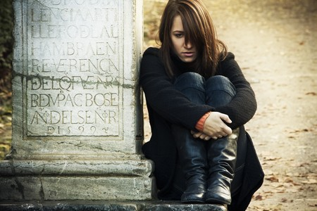 Sad woman sitting in a grave. Stock Photo