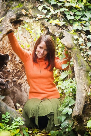 Young woman playing inside tree trunk. photo