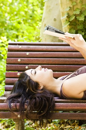 Reading woman laying in a park bench. photo