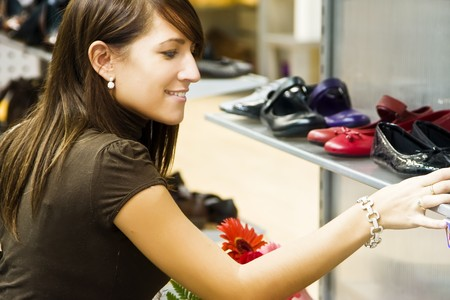 Young smiling woman choosing shoes.