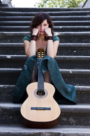 Young female guitarist on antique background photo