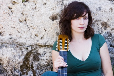 sited: Young female guitarist on antique background Stock Photo