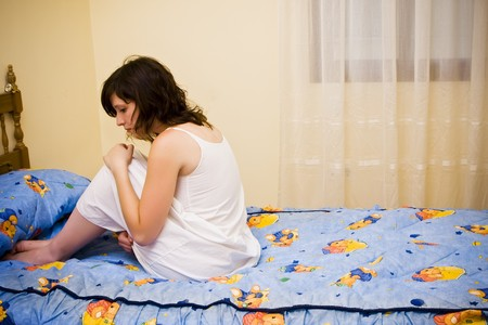 bedstead: Tormented young woman in her bedroom