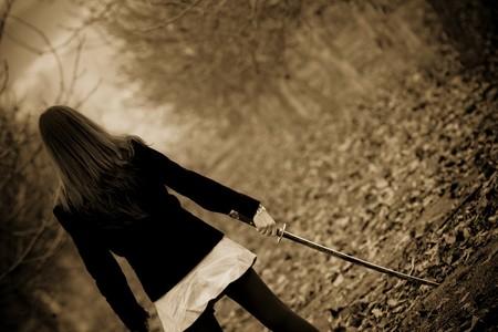katana: Young woman holding katana sword, sepia toned. Stock Photo