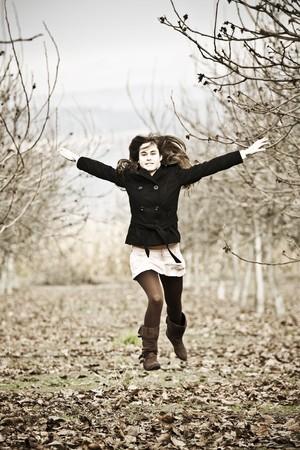 Young beautiful woman jumping in winter forest. photo