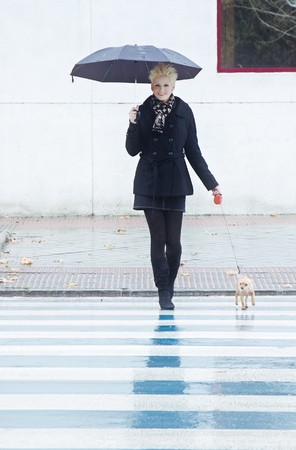 Young blond woman walking with her pet under rain. Stock Photo - 4084739