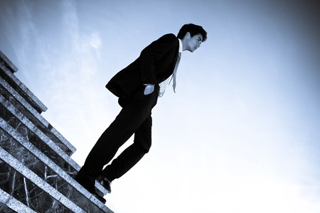 Businessman posing on stairs against blue sky. photo