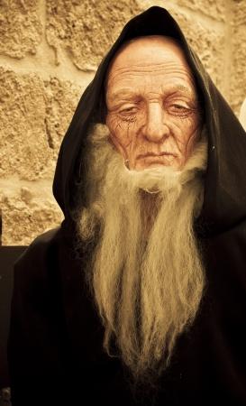 long beard: Old catholic monk figurine over stone background.