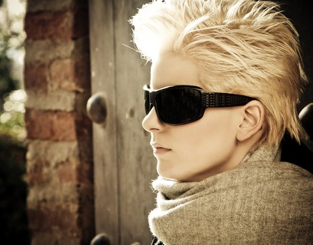 Young blond woman in winter fashion wearing sunglasses. photo