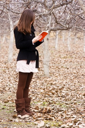Young unrecognizable woman reading a book in the forest. photo