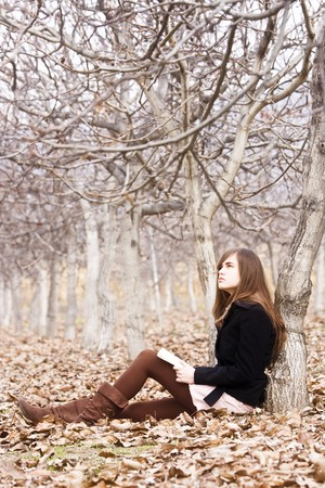 Young woman reading a book in the forest. photo