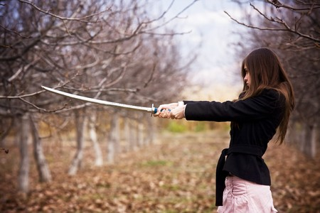 Young woman holding asian sword