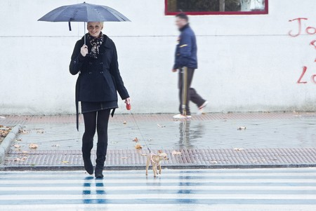 Young blond woman walking with her pet under rain. photo