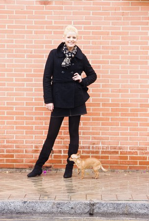 Young woman and small pet over urban background. photo