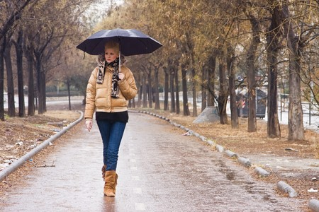 Young blond urban woman waling under rain photo
