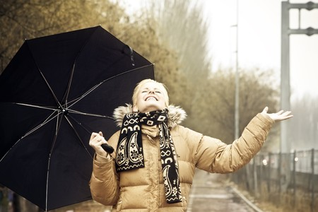 Happy young blond woman in a rainy day. photo