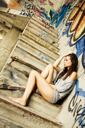 Worried young girl in unfinished stairs. Stock Photo
