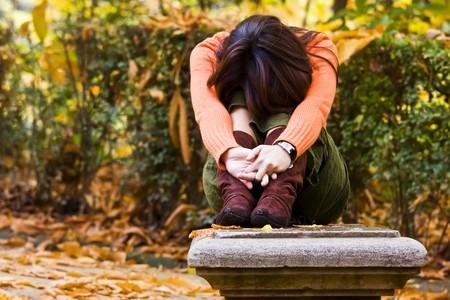 femme triste: Jeune femme assise entre couleurs d'automne. Banque d'images