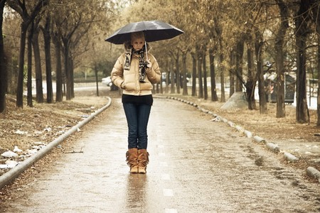 rainy day: Young blonde in walkway under rain Stock Photo