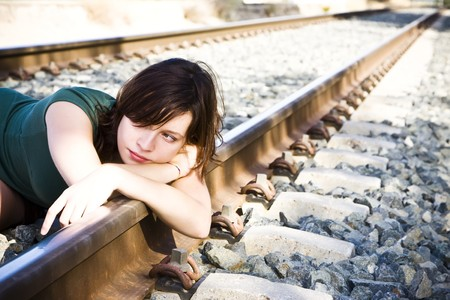 unintelligent: Sad young woman laying on the railway. Stock Photo