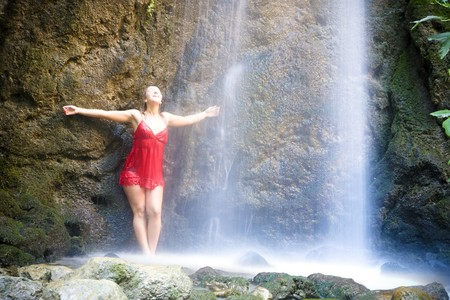sexual pleasure: Blond young woman under long exposed waterfall