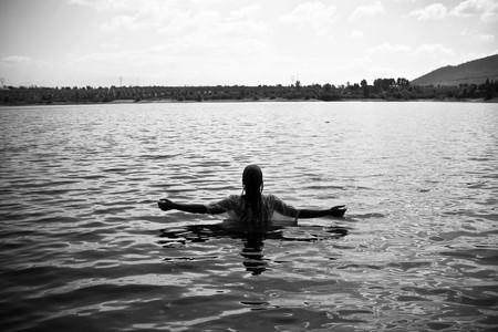 manos levantadas al cielo: Mujer joven con armas planteadas en el agua. Blanco y negro. Foto de archivo