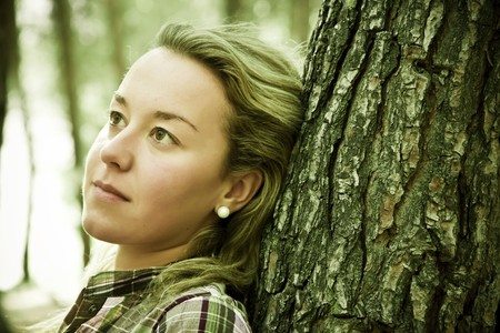 reflexive: Young thoughtful blonde in the forest.