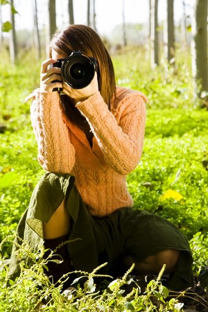 Young female photographer aiming at camera. Stock Photo