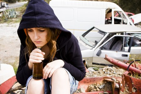 problematic: Young woman taking beer in the scrapyard Stock Photo