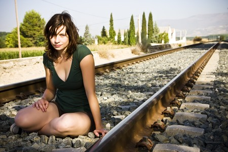 unintelligent: Young beautiful woman sitting on railtrack