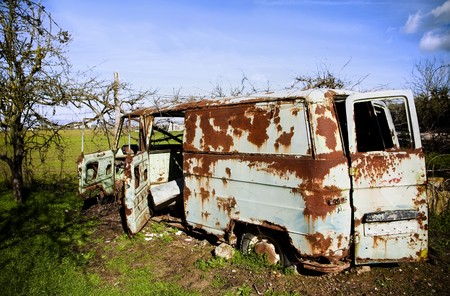 Rusty abandoned van in green field. photo