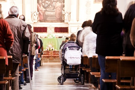 catholic chapel: Blurred people in cathedral, focus on baby trend.