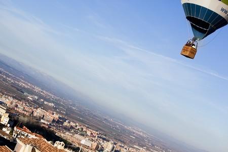unrecognizable people: Unrecognizable people in balloon basket flying over city