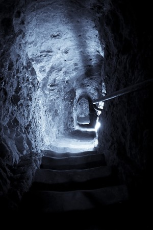 cave exploring: Stone steps to underground, blue toned.