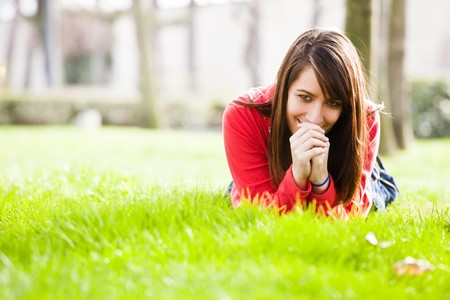 Smiling young woman laying in the grass. photo