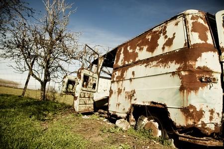 Rusty abandoned van in green field. photo