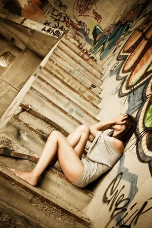 remorse: Young desperate woman in urban deteriorated place. Stock Photo