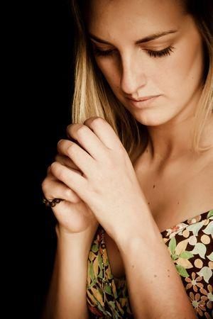 Blond praying woman against black background photo